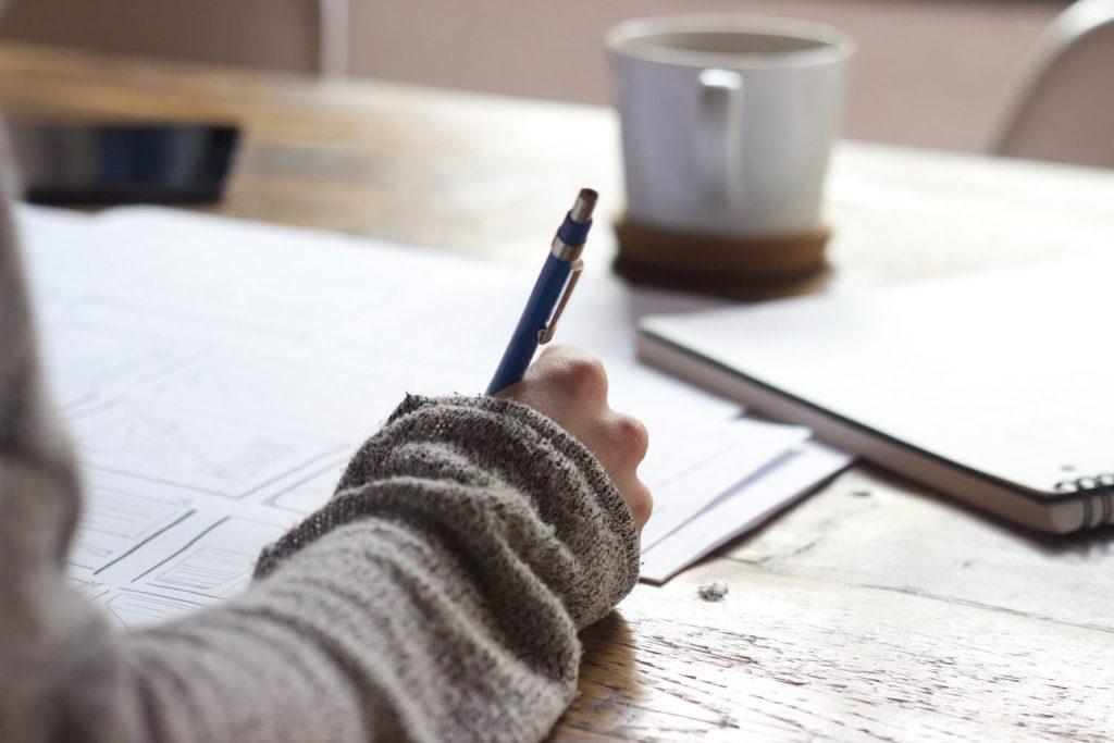 Frau schreibt mit einem Stift - Officemanagement - Virtuelle Assistenz